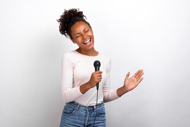 De grappige zanger van de mulatvrouw houdt een microfoon in haar handen