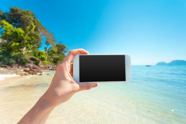 De greep witte mobiele telefoon van de vrouwenhand met mooie verse overzees en blauwe hemel in