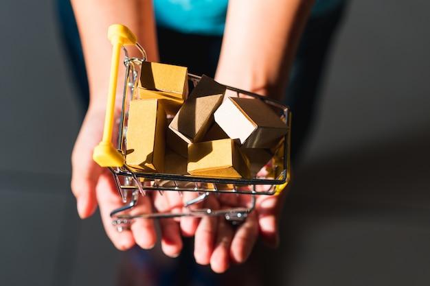 De greepdocument van de close-uphand doos in miniboodschappenwagentje die als elektronische handel gebruiken