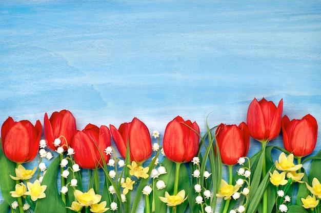 De grens van rode tulpen, gele narcissen en lelietje-van-dalen bloeit op plattelander