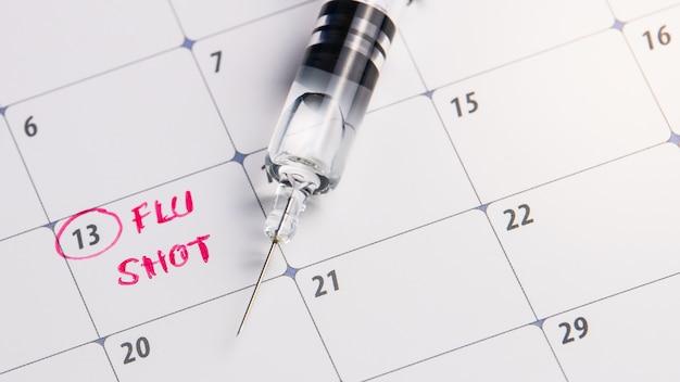 De griep van de artsenherinnering in kalender met spuit, geneeskunde en vaccinconcept wordt geschoten dat