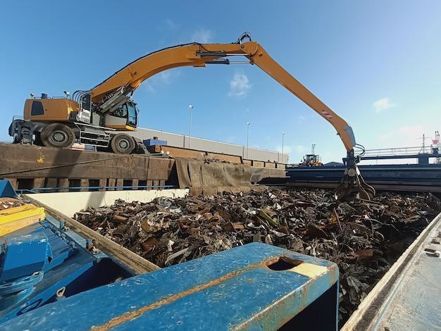 De grijper laad- en loskraan lost metaal en metaalafval voor recycling van de schepen