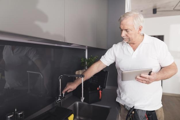 De grijze loodgieter staat in de keuken naast de kraan.