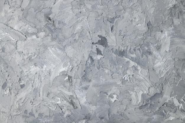 De grijze muur van de textuurgipspleister voor achtergrond en ruimte voor tekst