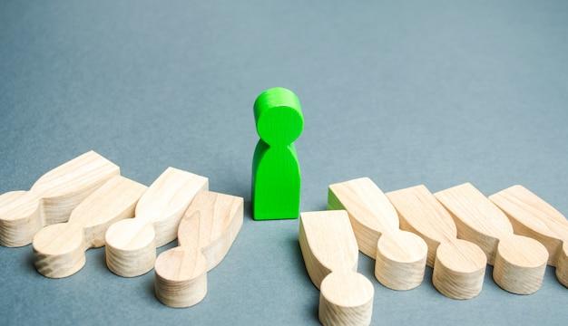 De groene gestalte van een man staat tussen de leugenachtige mensen. succesvolle keuze.