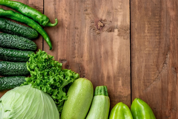 De groene groenten op houten tafel