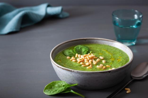 De groene romige soep van de bloemkoolspinazie op grijs
