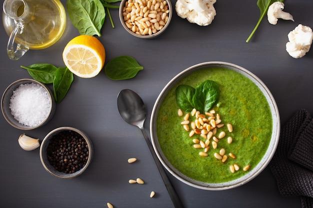 De groene romige soep van de bloemkoolspinazie op grijze achtergrond