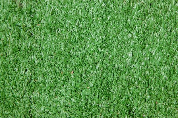 De groene texturen en de achtergrond van het kunstgrasveld het gras dat voor tuin en voetbalgebied wordt gebruikt