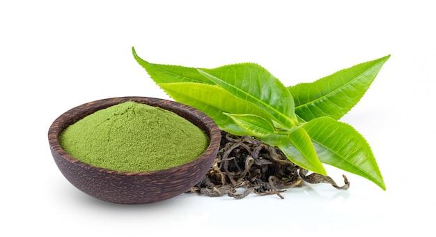 De groene thee van poedermatcha in kom met blad dat op wit wordt geïsoleerd