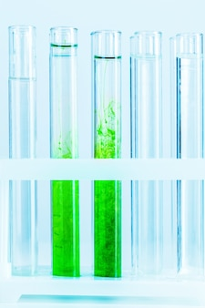 De groene vloeistoffen in reageerbuizen in chemisch laboratorium sluiten omhoog
