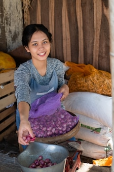 De groenteman glimlachte terwijl hij de sjalotten op traditionele weegschalen op de markt woog