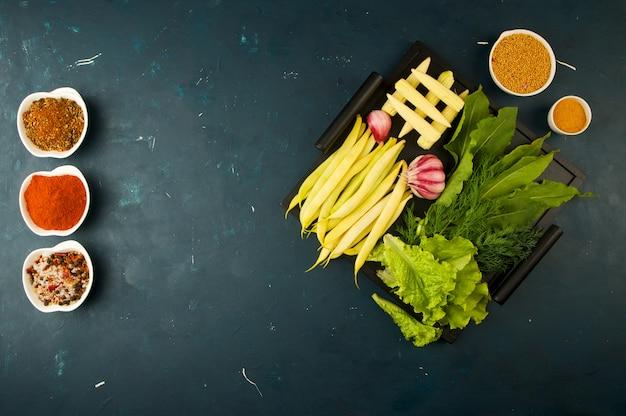 De groenten in de doos op de steen een donker. jonge greens ui knoflook zucchini heldere kruiden liggen in een houten lade met handvaten op een donker geweven.