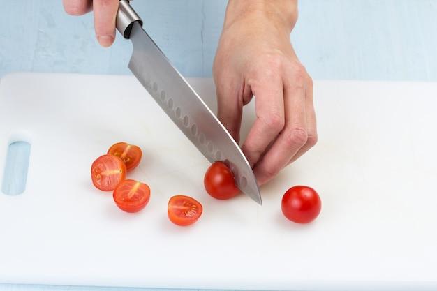 De groenten snijden met een keukenmes op het bord