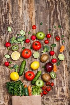 De groenten uit een papieren zak op houten tafel