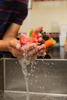 De groenten van de vrouwenwas op het aanrecht dichtbij om in een modern keukenbinnenland te dalen