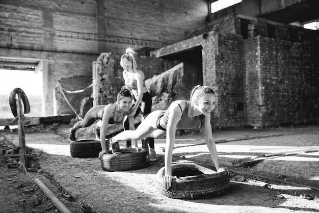 De groep aantrekkelijke meisjes doet opdrukoefeningen in verlaten plaats.