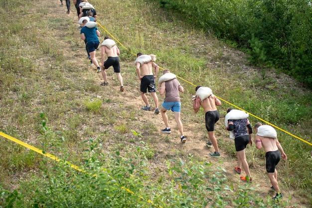 De groep atleten met zakken op zijn schouder beklimt berg