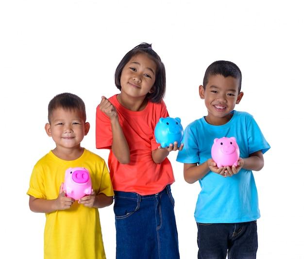 De groep aziatische kinderen heeft pret met geïsoleerd spaarvarken op wit