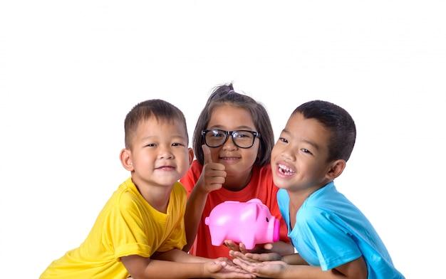 De groep aziatische kinderen heeft pret met geïsoleerd spaarvarken op witte achtergrond