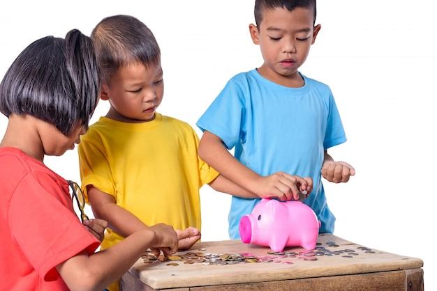 De groep aziatische kinderen heeft pret met spaarvarken op witte achtergrond wordt geïsoleerd die