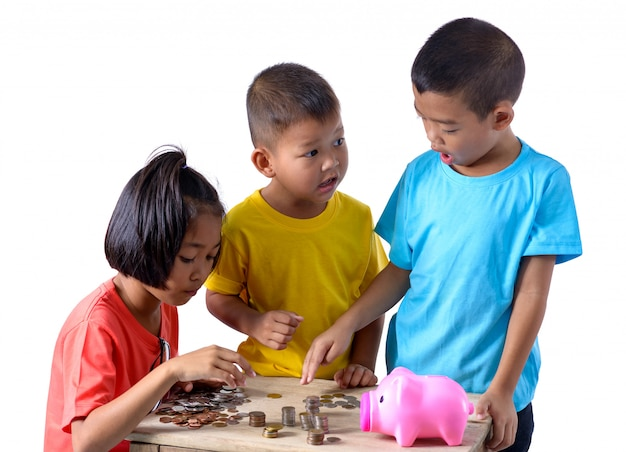 De groep aziatische kinderen helpt het zetten van muntstukken in geïsoleerd spaarvarken op wit