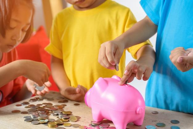 De groep aziatische kinderen helpt muntstukken zetten in o van het spaarvarken