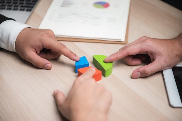 De groep bedrijfsmensen die puzzel assembleren en vertegenwoordigt teamsteun en hulpconcept