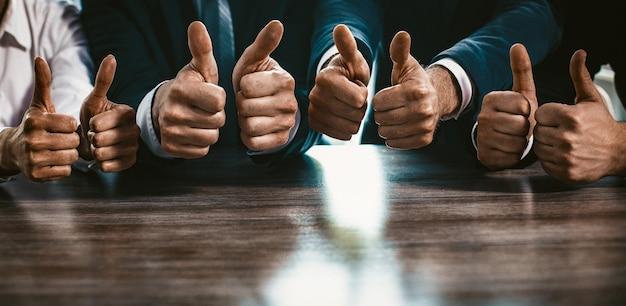 De groep bedrijfsmensen toont duimen omhoog gebaren, omhoog sluiten