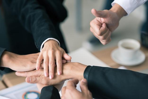De groep bedrijfsmensen verenigde handen samen en hief duim op, uitdrukken positief, t