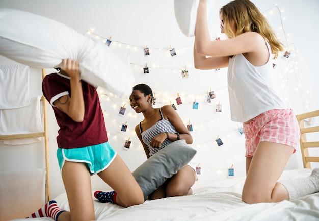 De groep diverse vrouwen die hoofdkussens spelen vecht samen op bed