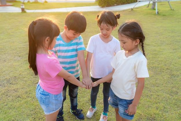 De groep gelukkige jonge aziatische kinderen stapelt of stapelt handen samen buiten in de speelplaats van het stadspark in de zomerdag. kinderen en recreatie concept.
