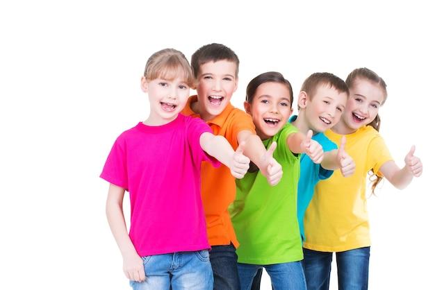 De groep gelukkige jonge geitjes met duim ondertekent omhoog kleurrijke t-shirts die zich verenigen - geïsoleerd op wit.
