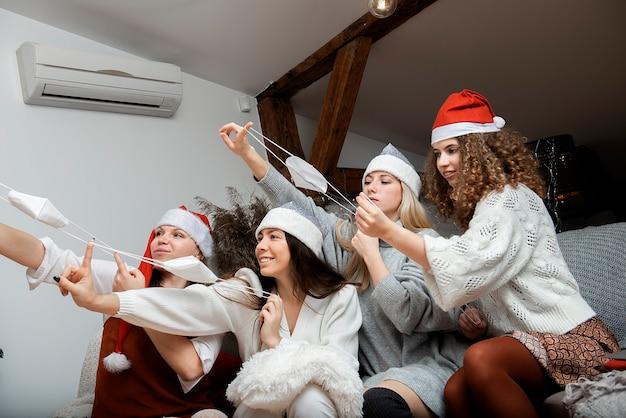 De groep gelukkige vrienden van vrouwenmeisjes in de hoeden van kerstmissanta en gezichtsmaskers neemt een vakantiezelfportret
