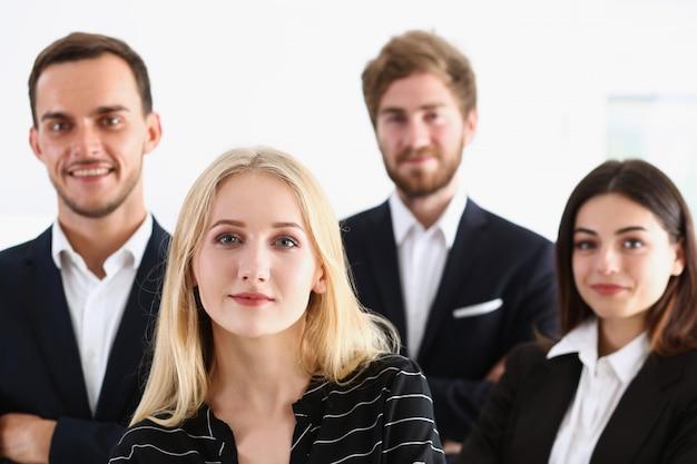 De groep glimlachende mensen bevindt zich in bureau het kijken