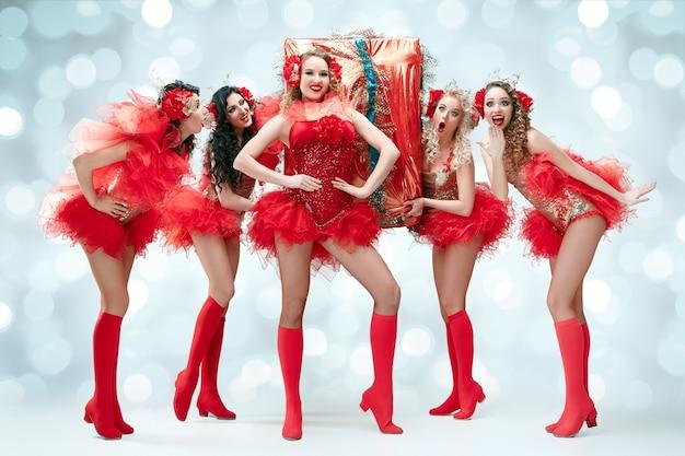De groep jonge gelukkig lachende mooie danseressen met carnaval jurken poseren met grote gift op blauwe studio achtergrond