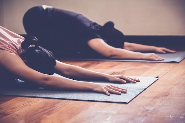 De groep jonge gezonde aziatische vrouwen die yogales, kind uitoefenen stelt met instructeur in huisstudio.