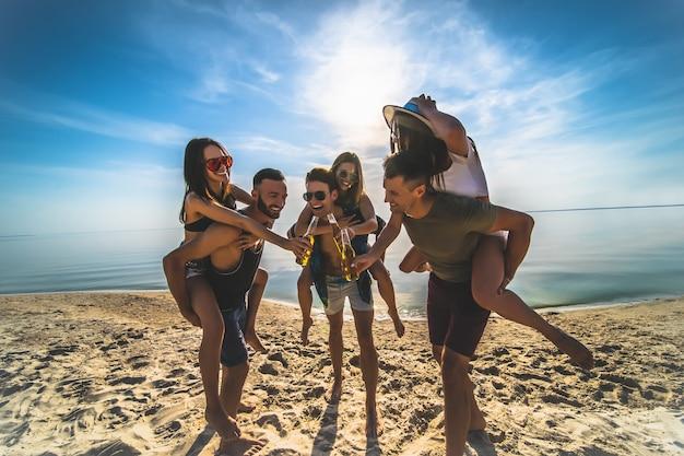 De groep jonge mensen die plezier hebben op het strand