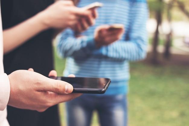 De groep jonge vriendentieners mobiel gebruiken bij stadsstraat