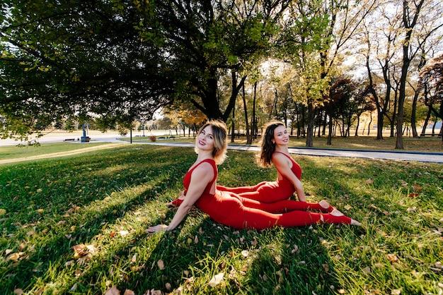 De groep jonge vrouwen maakt achteruit kromming ochtend in park terwijl zonsopgang. groep mensen zijn activiteit mediteren bij daw. zonnestralen schijnen in de camera