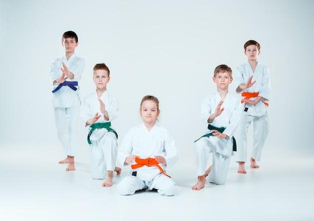 De groep jongens en meisjes die vechten op aikido-training op een vechtsportschool. gezonde levensstijl en sport concept
