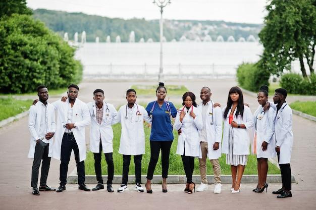 De groep medische studenten stelde openlucht in witte laboratoriumlagen