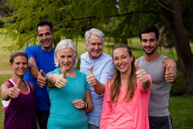 De groep mensen die samen duimen tonen ondertekent omhoog