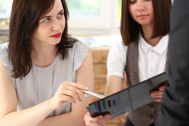 De groep mensen in bureau bekijkt mobiele tabletpc