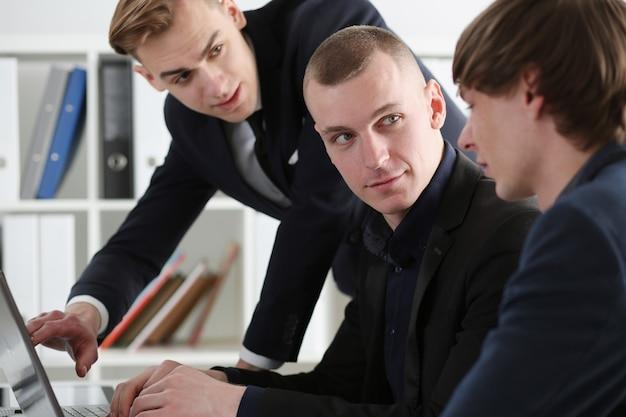 De groep mensen in bureau kijkt in laptop