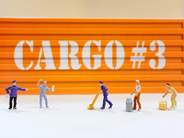 De groep miniatuurmensenarbeiders komt met ladingscontainer voor bij warehoue, industrieel en logistiek concept