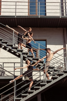 De groep moderne balletdansers die op de treden bij de stad presteren