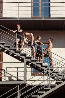 De groep moderne balletdansers die optreden op de trappen in de stad