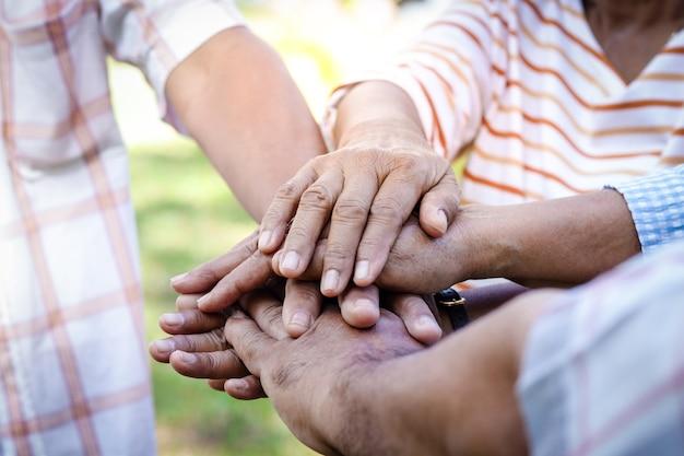 De groep ouderen slaat de handen ineen een gelukkig leven na pensionering. ouderling gemeenschapsconcept