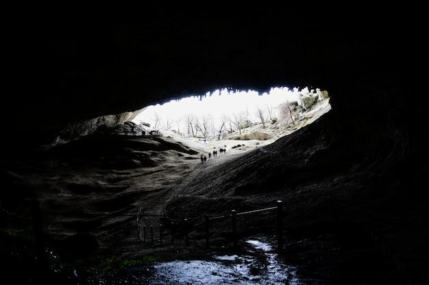 De groep reizigers die binnen het onderstel van enorme grot in torres del paine nationaal lopen